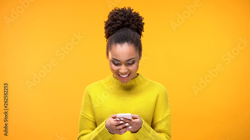 Obraz Smiling African-American woman chatting on smartphone, modern technology, app - fototapety do salonu