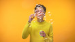 Joyful black woman blowing soap bubbles on yellow background, youth happiness