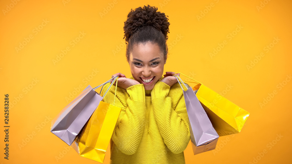 Fototapety, obrazy: Excited young woman in stylish yellow sweater holding shopping bags, discount