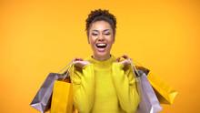 Joyful Female Shopaholic Holding Purchase Bags Yellow Background, Style Fashion