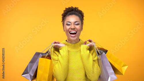 Photo  Joyful female shopaholic holding purchase bags yellow background, style fashion