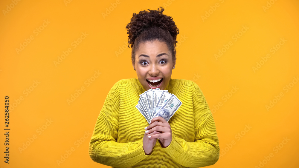 Fototapety, obrazy: Excited Afro-American woman holding bunch of dollars, lottery winner, fortune