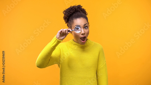 Curious afro-american woman looking magnifying glass, having fun, surprise Fototapet