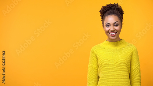Fotografiet  Positive young woman standing on bright background, pretty female teenager