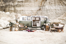 Wedding Decor In Boho Rustic Style. Green Hippie Bus, Decorated Sofa, Armchair, Carpets, Pillows, Table With Candles, Succulents, Plant Decoration On The Background Of Canyon Landscape
