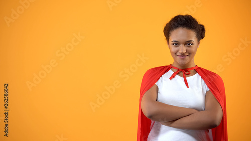 Confident young lady in red cape on bright background, powerful wonder woman Canvas Print