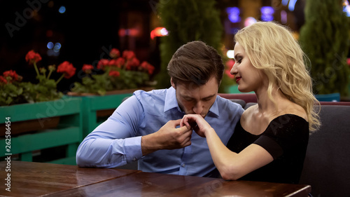 Amorous admirer kissing hand of his beautiful lady, sitting in cozy restaurant Wallpaper Mural