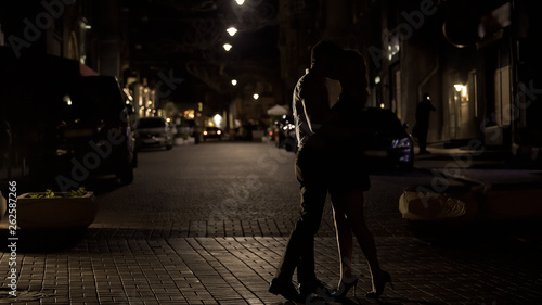 Two loving people kissing tenderly in night street, love in big city, dating
