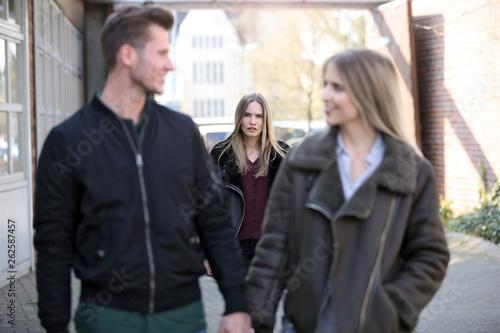 Fotografija Junge Frau beobachtet eifersüchtig ein Paar
