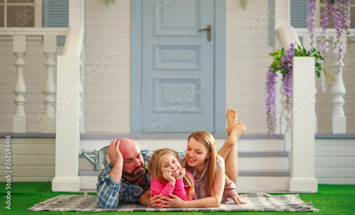 Vászonkép Young happy family having fun in courtyard of the summer house