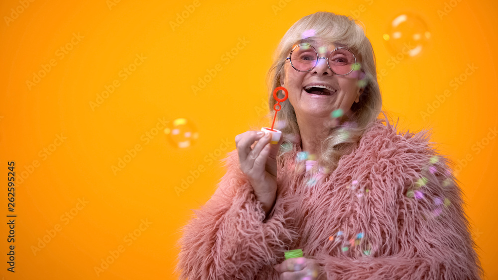 Fototapety, obrazy: Funny stylish granny in pink coat and round sunglasses making soap bubbles, ad