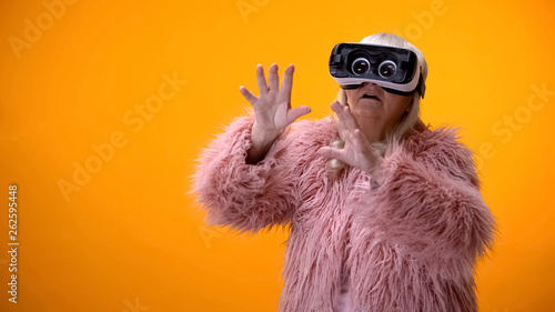 Fotografía  Senior woman in funny coat and VR headset playing video game, hi-end innovations
