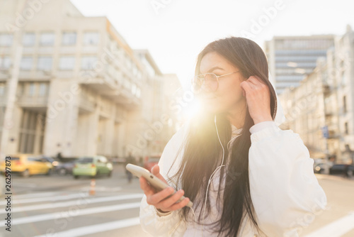Foto  Fashionable woman stands in the background of a city, smartphone in her hand, wears a white jacket and listens to music