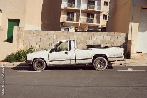 Obraz stary biały pickup na tle ściany na Malcie - fototapety do salonu