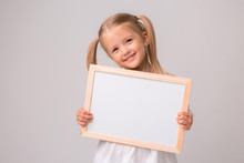 Girl Holding A White Board .Cute Little Girl With A White Sheet Of Paper.white Background.copy Spase.Little Girl Holding An Empty White Sheet,place For Text