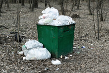 Old Rusty Metal Green Garbage Container Full With Plastic Waste Standing In City Park Or Forest. Environmental Pollution