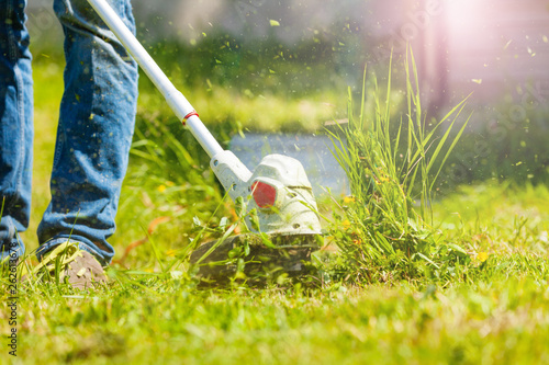 Fototapeta Man trimming fresh grass using brush cutter obraz