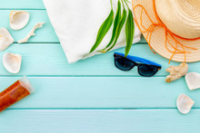 Straw Hat, Sun Glasses, Shells And Sunblock Cream For Sea Vacation On Mint Green Wooden Background Top View Copy Space