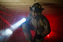 Firefighter In Confined Space With Smoke Searching For Victims With Large Flashlight