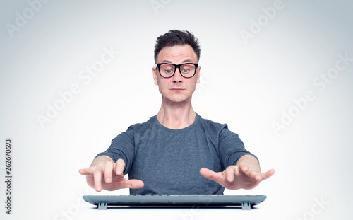 Man in glasses working at the computer, his hands hover over the keyboard while typing Wallpaper Mural