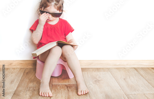 Canvas Print funny child girl sitting on chamberpot, Children's legs hanging down from a pot