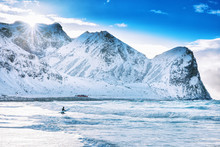 Iconic Arctic Surf Beach - UNSTAD, Located Over Polar Circle In Norway, Moskenes On Lofoten Islands. Man Surfer Going With Surf Board Into Norwegian Sea Waters At Epic Rocks Background. Winter Season.