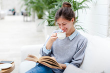 Young Woman Is Drinking Coffee And Reading Book. Girl Is Smiling, Enjoying Relaxation And Sitting On Sofa In Cozy Modern Cafe Indoors.