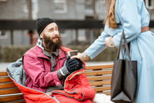 Woman Helping Homeless Beggar Giving Some Hot Drink Outdoors. Concept Of Helping Poor People