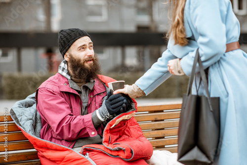 Woman helping homeless beggar giving some hot drink outdoors Fototapeta