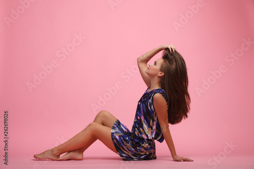 Fotografia  Beautiful young girl sitting in a pose on the floor in the studio, full length,