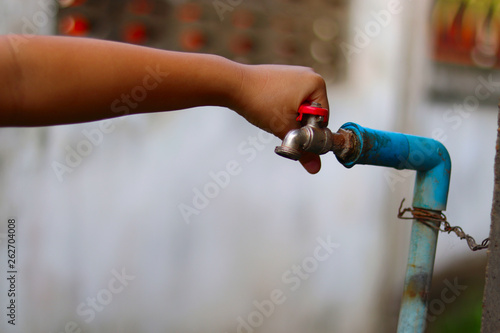 Foto  Young hands turning off an old rusty water tap for saving water - save water con