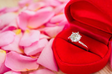 Elegant Wedding Diamond Ring In Red Heart Jewelry Box On Beautiful Pink Rose Petal Background Close Up