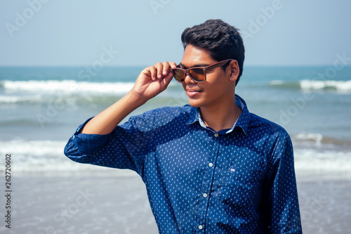 Photo  young hindu stylish man posing with sunglasses active beach vacation on semmertime happy Goa India beach