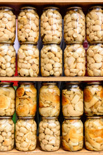 Delicious Delicious White Marinated Mushrooms In Glass Jars On Shelves.