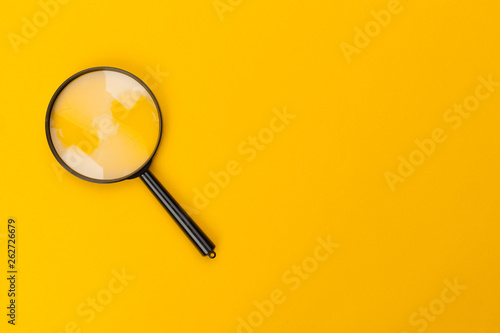Fotomural  magnifying glass on yellow background
