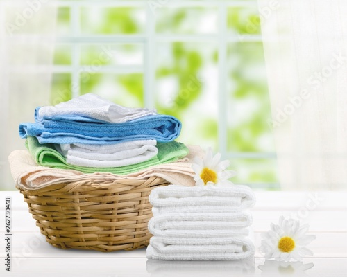 Fotografia  Laundry Basket with colorful towels on background