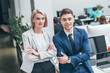 two young business partners with crossed hands smiling and looking at camera