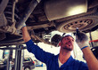 car service, repair, maintenance and people concept - auto mechanic man or smith with flashlight working at workshop