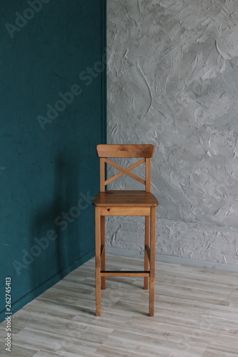 Foto  Wooden chair on a gray wall background