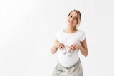 Fototapeta Panels - Beautiful young pregnant woman posing isolated over white wall background holding little shoes.