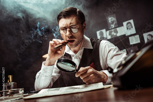 Detective in glasses smoking cigar and reading newspaper with magnifier in offic Wallpaper Mural