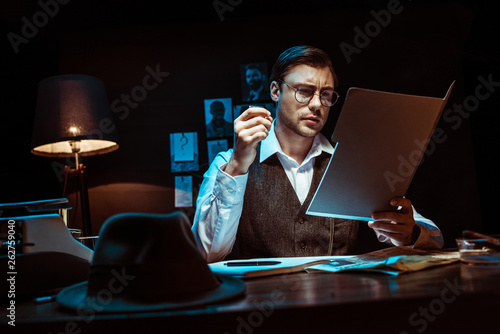 Valokuva  Concentrated detective in glasses reading dossier in dark office