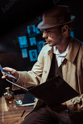 Photo Stands Music Band Detective in trench coat and hat holding dossier and looking at photo
