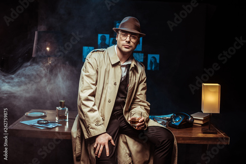 Pinturas sobre lienzo  Detective in trench coat and hat sitting on table and holding glass of cognac