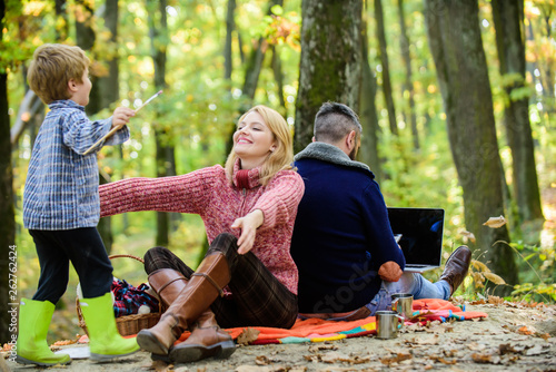 Poster Camping Dad is always busy. Family day concept. Family with kid boy relaxing in forest. Mother and little play together while father working with laptop. Conflicts of being dad. Family and career goals