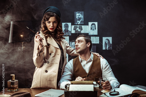 Fotografía  Woman with mouthpiece standing near detective in dark office