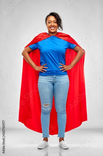 Fotografia super power and people concept - happy african american young woman in superhero