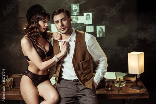 Fotomural Sexy woman in black lingerie sitting on wooden table and flirting with detective