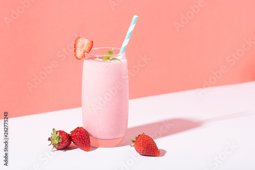 Strawberry smoothie in glass with straw and scattered berries on pink background.