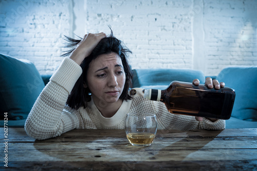 Young, sad, unhappy, helpless woman drinking alcohol Canvas Print